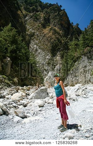 sport hiking or trekking woman with green shirt purple trousers green cap standing in Gorge Samaria natural park mountain in Crete Greece Europe