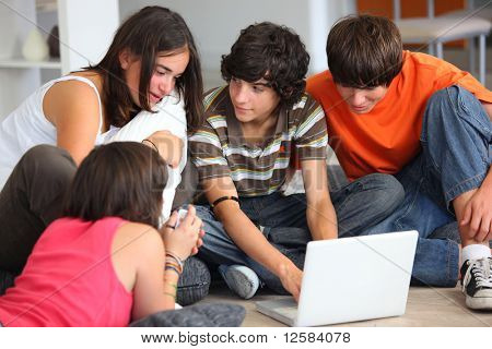 Group of teenagers sitting on the floor in front of a laptop computer