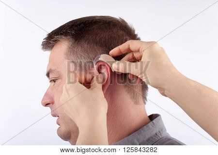 Audiologist inserting a hearing aid into a senior man's ear