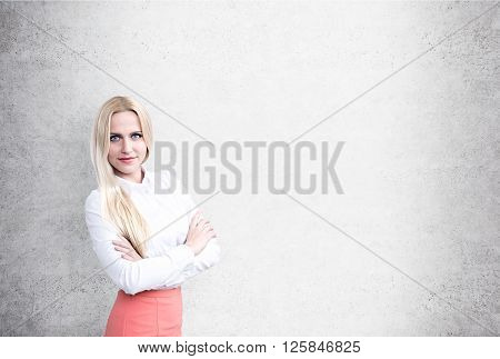 Pretty busineswoman in shirt and pink skirt with blank concrete wall in the background. Mock up