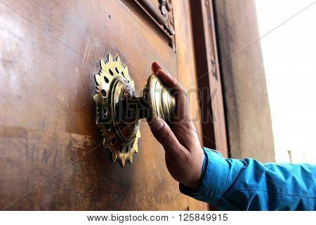 Old bronze door handle pushed by mans hand. Polished bronze door handle on the wooden door. Mans' hand touches the door handle.