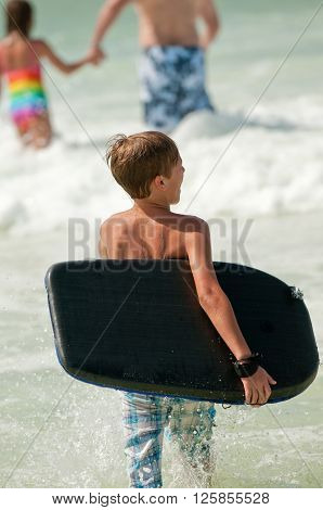 Young boy going out into the ocean to body surf and boogie board.