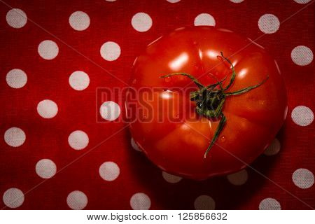 One red tomato lying on the red tea-towel