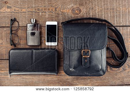 Top view photo of objects on wooden table. There are mobile phone, men's purse, glasses, perfume and bag