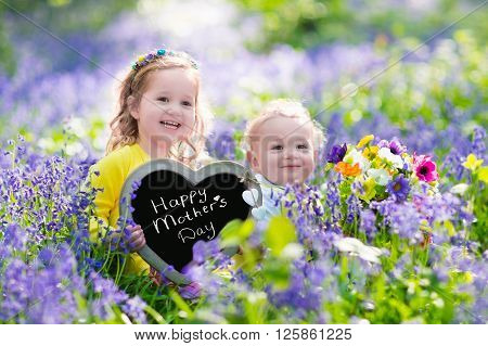 Children playing in bluebell flowers. Little girl and baby boy hold wooden heart shape chalk board. Copy space for your text. Kids having fun outdoors. Birthday or mother's day celebration.
