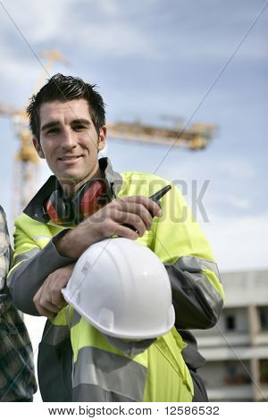 Portrait of a young man with safety vest and noise-canceling headphones