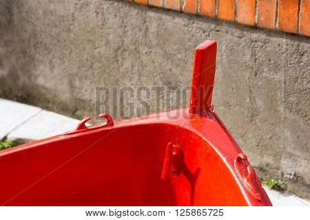 Detail of a wooden red prow of a rowing boat moored on pier. Liguria Italy