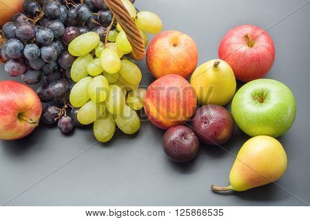 Mix of various fresh ripe fruits top view plums peaches pears apples and grapes on gray neutral background