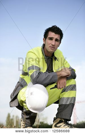 Portrait of a young worker with safety helmet crouching
