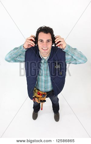 Portrait of a young worker with noise-canceling headphones on white background