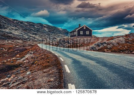 Norway high mountains landscape with road and house. Dramatic film style colors.