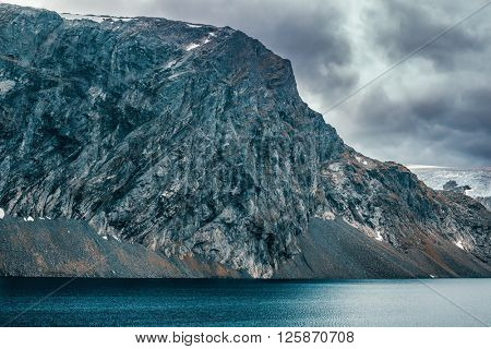 Norway high mountains cold and severe landscape. Big mountain over lake.