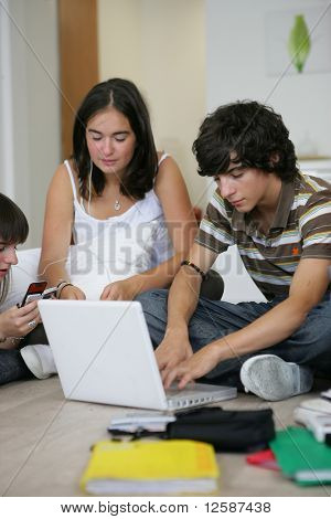 Boy sitting in front of a laptop computer near two girls listening to music