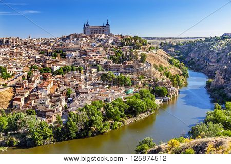 is Alcazar Fortress Medieval City Tagus River Toledo Spain. Toledo Alcazar built in the 1500s Destroyed in Spanish Civil War and then rebuilt after war. Unesco historical site; Tagus is longest river in Spain.