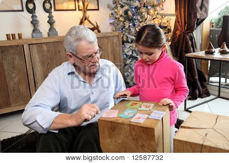 Senior man playing cards with little girl