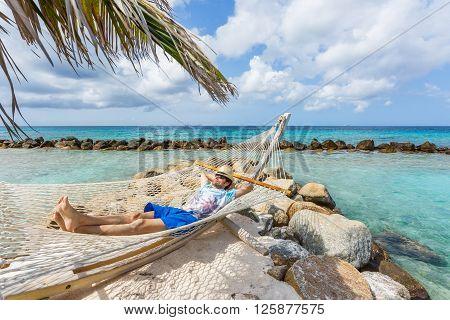 Man in hat in a hammock on caribbean beach