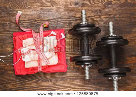 Pair of sneakers measuring tape and dumbbells wooden background