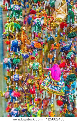 The colorful wind chimes with toy elephants dolls and different beads in market stall Jerusalem Israel.