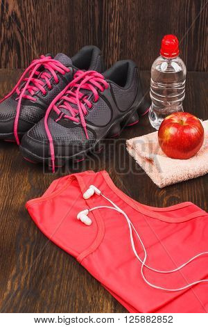Apple sneakers towel and bottle of water wooden background