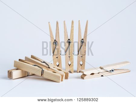 Wooden clothespins on a white batskground close-up tools
