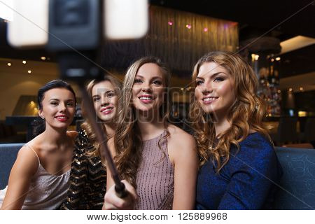 celebration, friends, bachelorette party, technology and holidays concept - happy women with smartphone selfie stick taking picture at night club