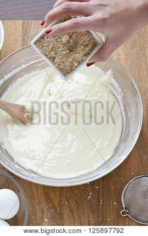Female Adding Brown Sugar Into A Paste