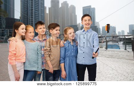 childhood, friendship, technology and people concept - group of happy children talking picture by smartphone on selfie stick over dubai city street background