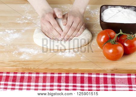 image of hand flattening the pizza dough