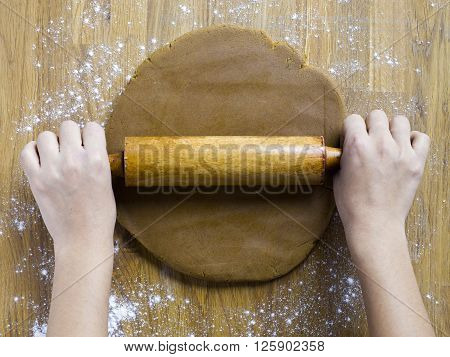 image of human hand rolling gingerbread dough