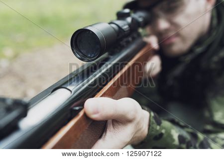 hunting, war, army and people concept - close up of young soldier, ranger or hunter with gun in forest