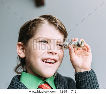 boy businessman looks through small tube from dollar smiling