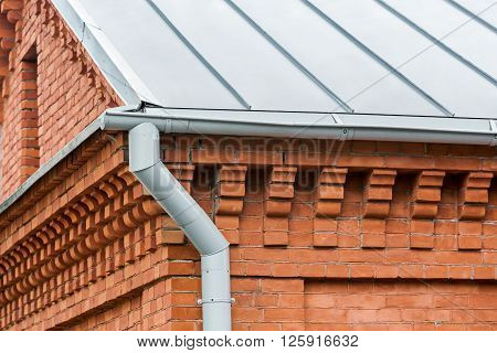 Drainpipe With Gutter On Red Brick Wall