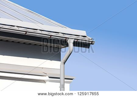 new gray metal rain gutter on house rooftop against blue sky poster