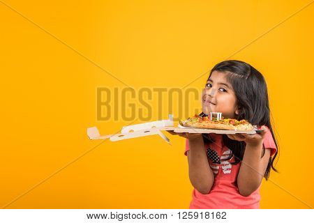 portrait of cute indian girl holding an open box of pizza, excited asian girl opening pizza box  showing smile on face, standing over yellow background