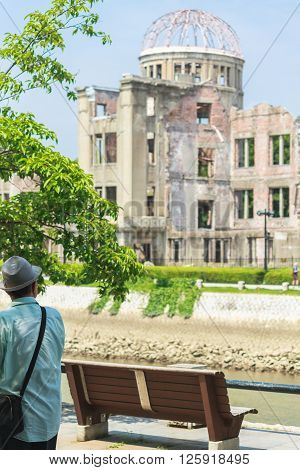 Hiroshima, Japan - July 10, 2014: A Japanese man walks past a bench next to the Aioi River across the Atomic Bomb Dome (Hiroshima Peace Memorial) that was destroyed by the Atomic Bombing of Hiroshima (