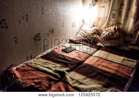 Night-lighted corner of the room with unmade double bed in warm colours.