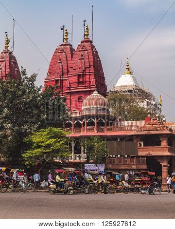 DELHI INDIA - 19TH MARCH 2016: A view of streets and the Shri Digambar Jain Lal Mandir Temple in Delhi. Lots of Rickshaws and people can be seen.