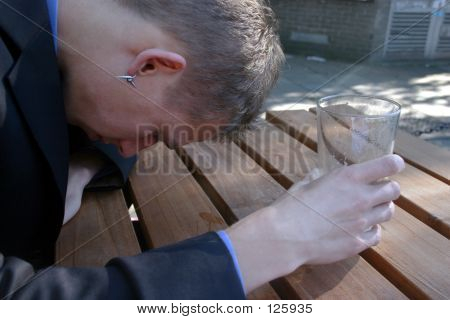 An Upset Young Man In A Suit Finishes His Beer.
