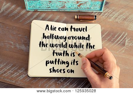 Handwritten quote A lie can travel halfway around the world while the truth is putting its shoes on, as inspirational concept image