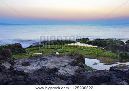 Sunset at Punta Secca Beach with rocks and green seaweeds in Santa Croce Camerina Sicily Italy