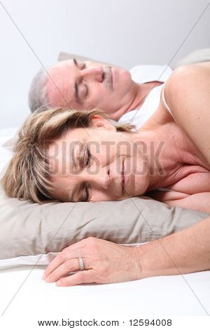 Senior couple laid in a bed