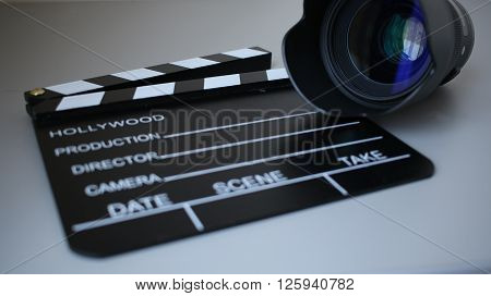 Cinemas clapperboard with a camera lens on it. Perfect composition for movie makers.