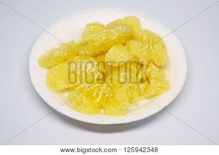 Cut of juicy pomelo isolated on white dish with white color background poster
