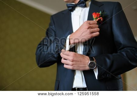 A man or groom cufflink buttons on a white shirt in room with natural light. Black wedding suit, bow-tie, watch on hand, indoors.