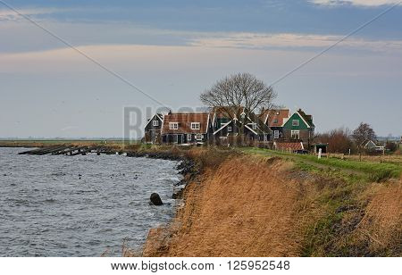 Marken is particularly colorful peninsula in the Markermeer, The Netherlands. This photo of a group of houses is taken from an embankment on December 20, 2015.