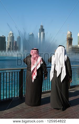 Dubai - February 72012:Two sheiks at the Dancing fountains.The Dubai Dancing fountains are world's largest fountains with height 150 m.