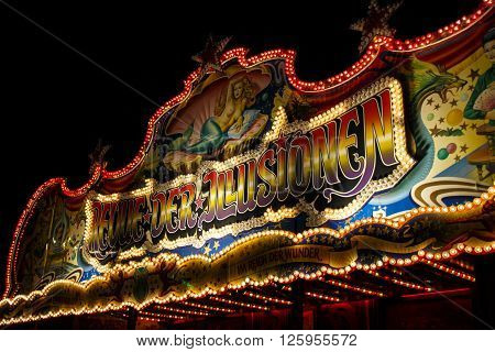 MUNICH, GERMANY - SEPTEMBER 18, 2015: Nightshot of the Revue der Illusionen building on Theresienwiese an entertainment show during Oktoberfest