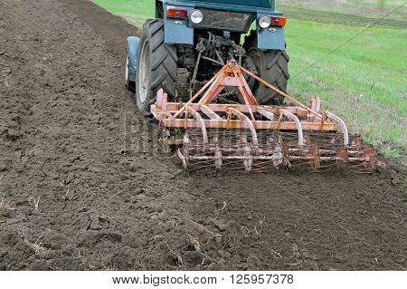 Tractor With Cultivator Harrow The Ground Fastened. Summer Season Opens Plowing And Cultivating The