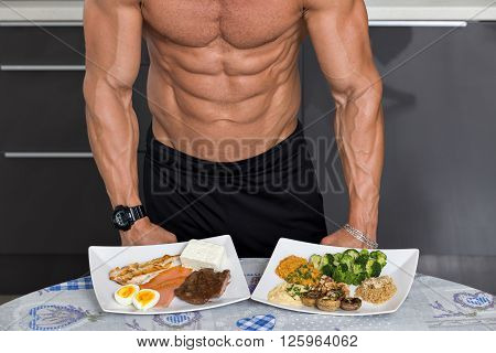 fit young man. bodybuilder in the kitchen; animal versus plant proteins: plate with beef eggs salmon cheese and chicken grill and another with nuts mushrooms broccoli lentil hummus and quinoa