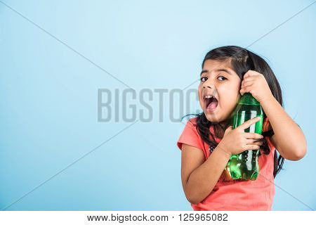 indian girl with cold drink bottle, asian girl drinking cold drink in pet bottle, girl kid and cold drink, indian cute girl with lemon or carbonated cold drink in plastic bottle, isolated on blue